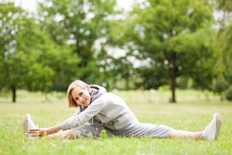 Frau, die draußen ausdehnt stockbilder