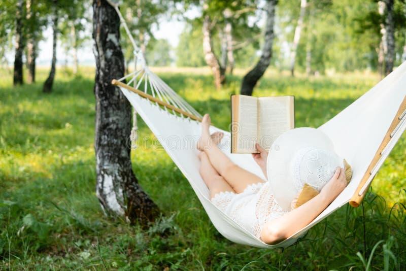 Frau, die draußen in der Hängematte stillsteht Entspannen Sie sich und das Buch lesend lizenzfreie stockfotos