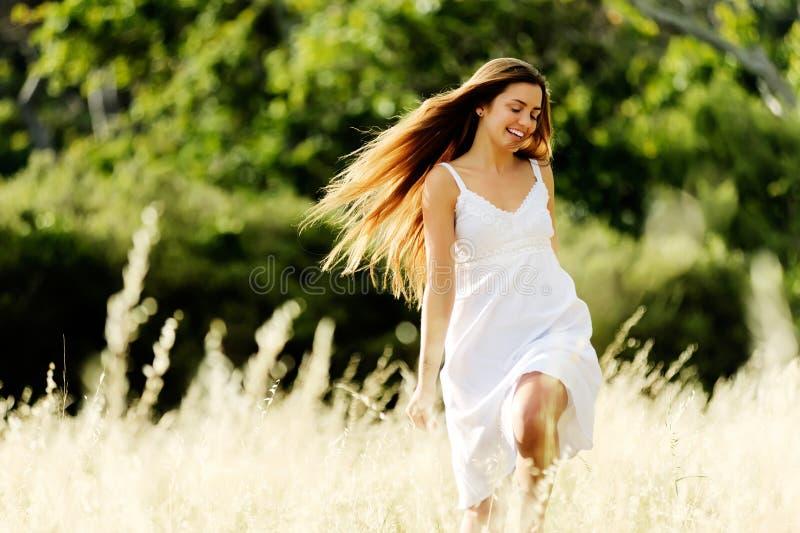 Frau, die draußen in ein Feld läuft stockbild