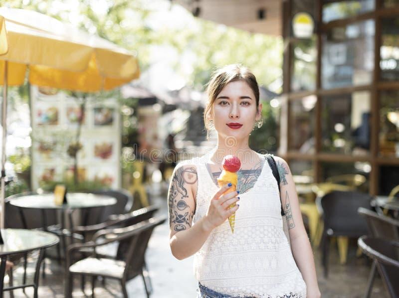 Frau, die draußen Eiscreme Entspannungs-zufälliges Konzept hält stockfoto