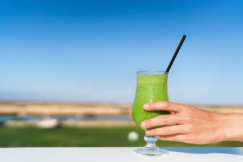 Frau, die draußen Glassaft des grünen Smoothie hält stockfoto