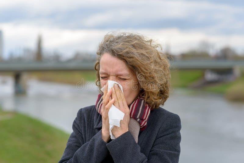 Frau, die draußen ihre Nase auf einem Gewebe durchbrennt lizenzfreie stockbilder