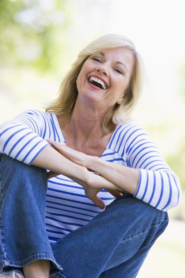 Frau, die draußen lachen sitzt stockfotografie