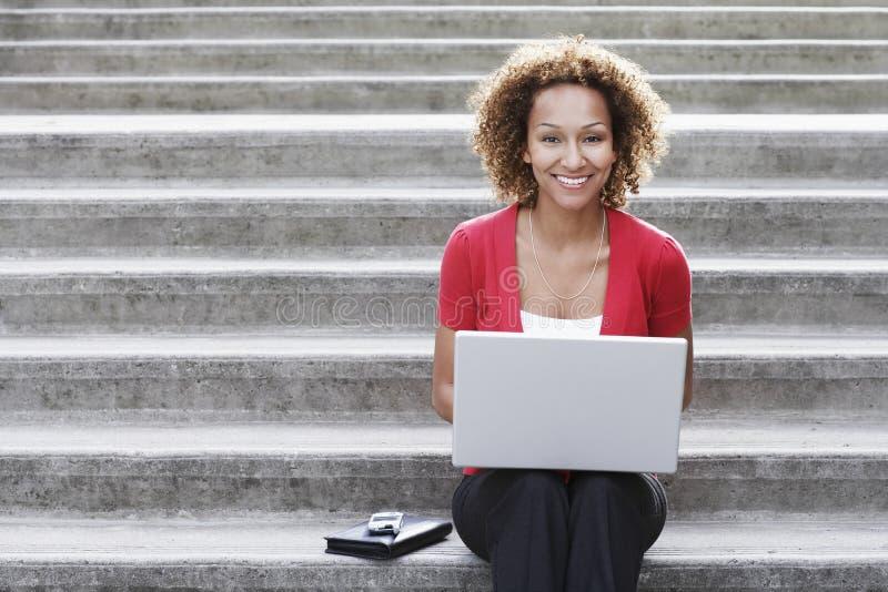 Frau, die draußen Laptop auf Schritten verwendet lizenzfreie stockbilder
