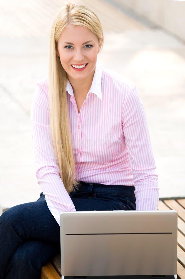 Frau, die draußen Laptop verwendet stockfotografie
