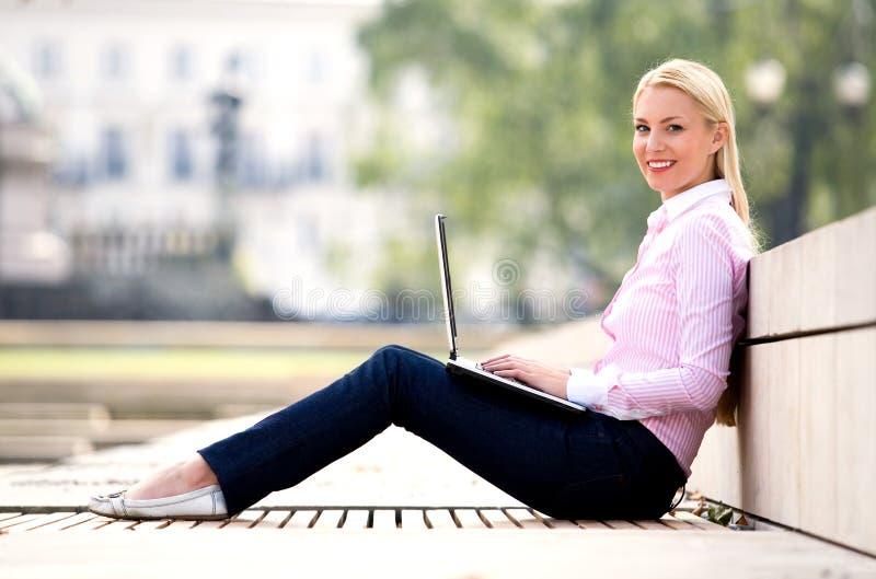 Frau, die draußen Laptop verwendet lizenzfreie stockfotografie