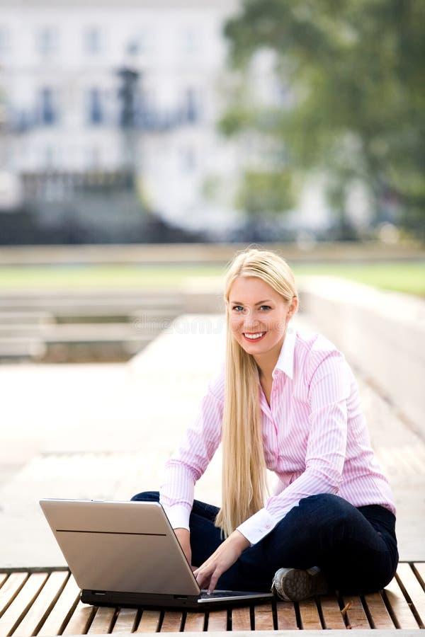 Frau, die draußen Laptop verwendet lizenzfreie stockbilder