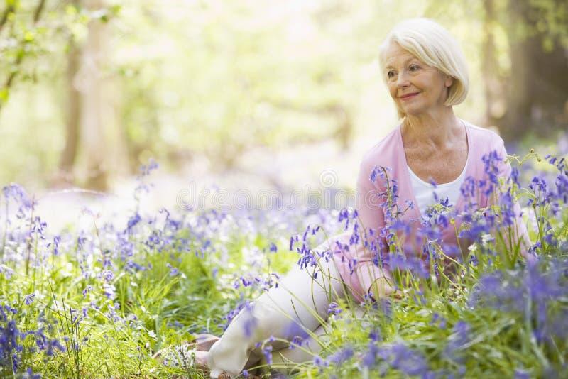 Frau, die draußen mit dem Blumenlächeln sitzt lizenzfreie stockfotos