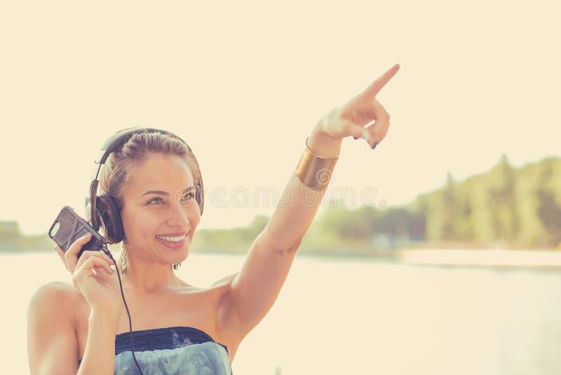 Frau, die draußen Musik hört stockfotos
