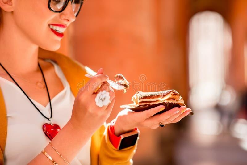 Frau, die draußen Tiramisu isst stockbilder