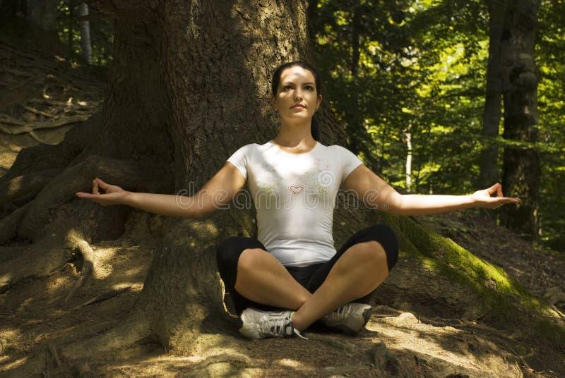 Frau, die draußen Yoga in Lotosstellung tut lizenzfreie stockfotos