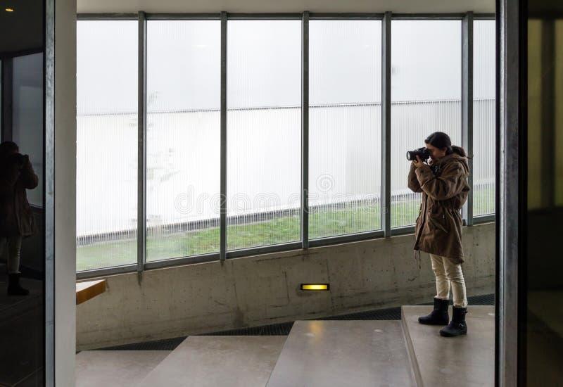 Frau, die dslr Kamera im Gebäude verwendet lizenzfreie stockfotos