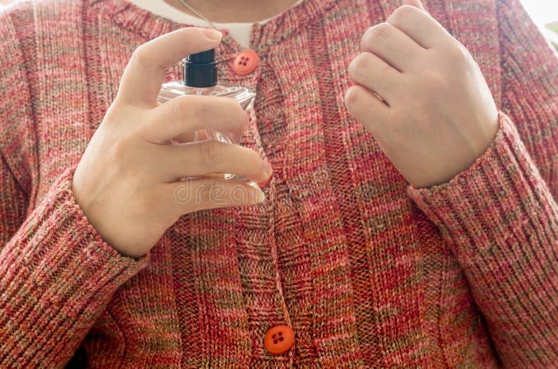 Frau, die Duftstoff auf Handgelenk anwendet lizenzfreie stockfotografie