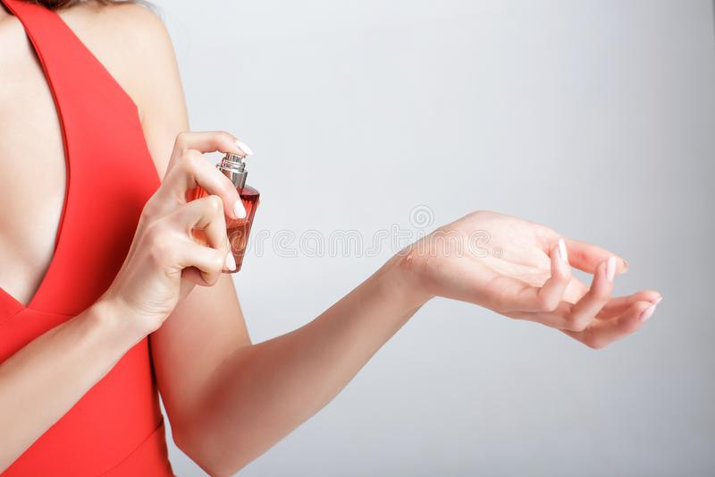 Frau, die Duftstoff auf ihrem Handgelenk anwendet lizenzfreie stockfotos