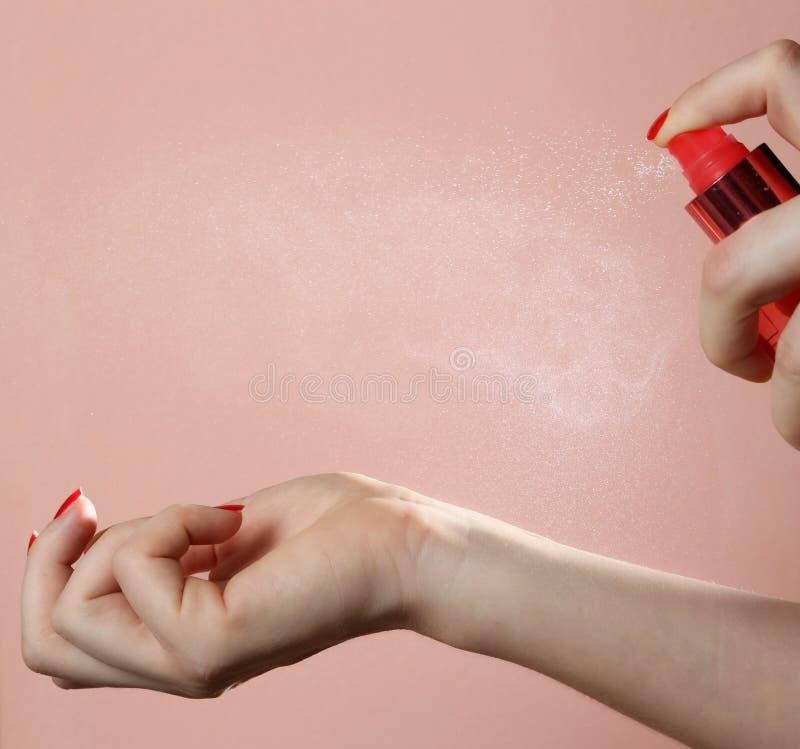 Frau, die Duftstoff auf ihrem Handgelenk anwendet stockfotos
