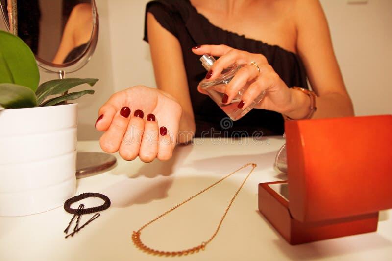Frau, die Duftstoff auf ihrem Handgelenk anwendet lizenzfreie stockbilder