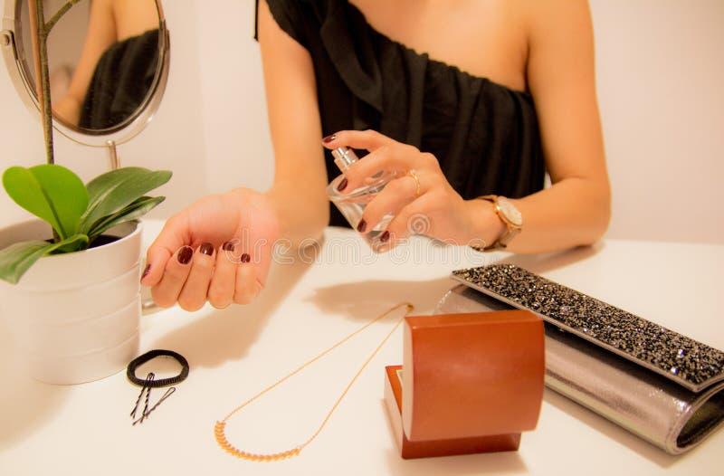 Frau, die Duftstoff auf ihrem Handgelenk anwendet stockbild