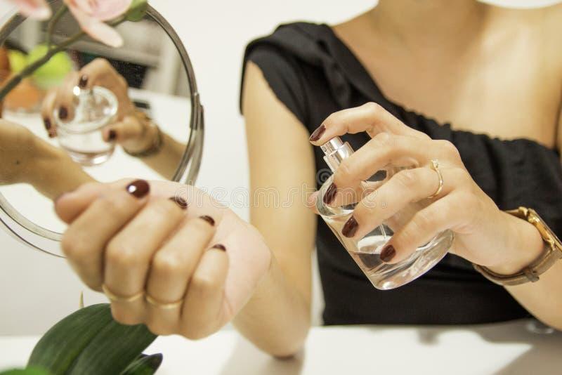 Frau, die Duftstoff auf ihrem Handgelenk anwendet stockbilder