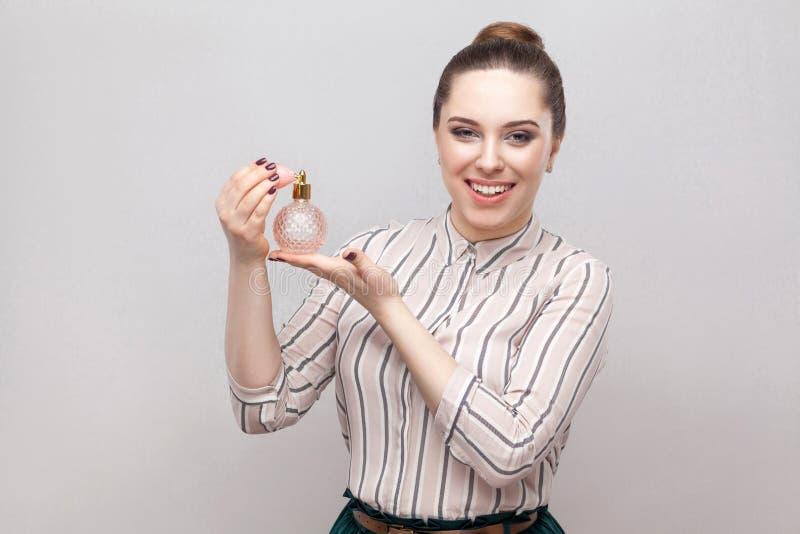 Frau, die Duftstoff verwendet Lächelndes Sprühparfüm der attraktiven Frau, das Aromaduft-Holdingflasche Parfümgrau genießt stockbilder