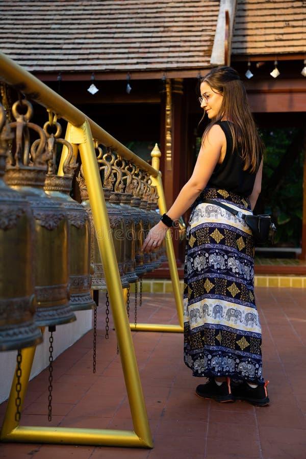 Frau, die durch ausgerichtete Eisenglocken in einem thailändischen Tempel mit Sonnenlicht geht lizenzfreie stockbilder