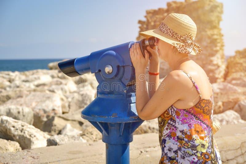 Frau, die durch Binokel schaut lizenzfreies stockbild