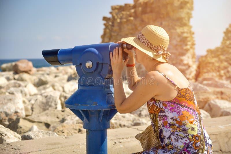 Frau, die durch Binokel schaut lizenzfreie stockbilder