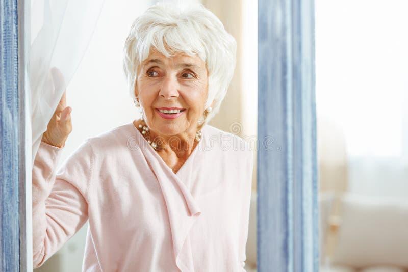 Frau, die durch das Fenster lugt stockfoto