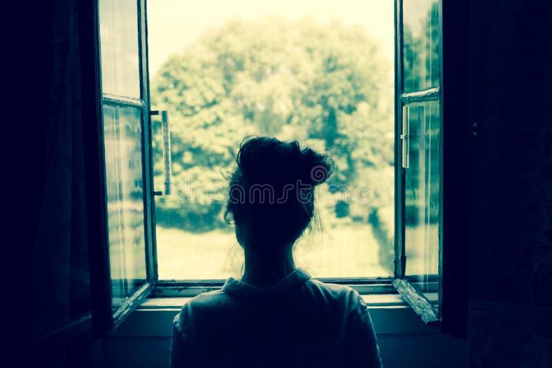 Frau, die durch das Fenster schaut lizenzfreie stockfotografie