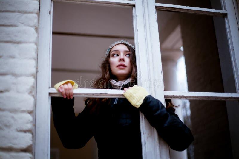 Frau, die durch das Fenster und das Befürchten von etwas schaut stockbild