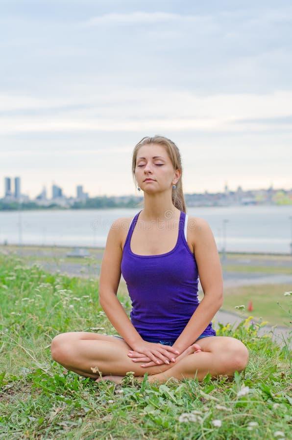 Frau, die durch das Meer meditiert lizenzfreie stockbilder