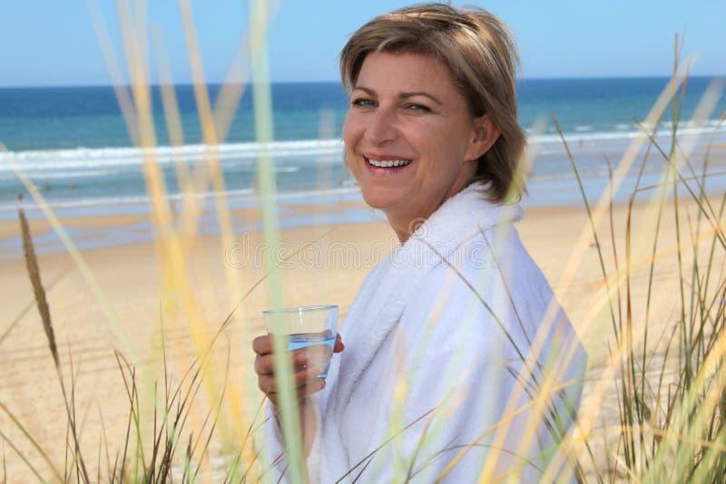 Frau, die durch das Meer sich entspannt lizenzfreie stockfotografie