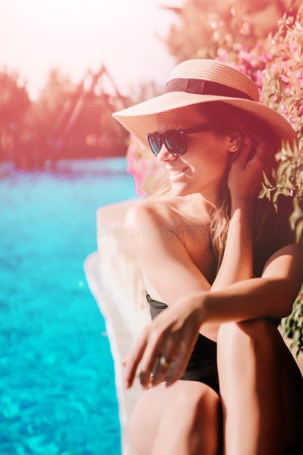 Frau, die durch das Pool und die Entspannung, erhalten sitzt gebräunt stockbilder