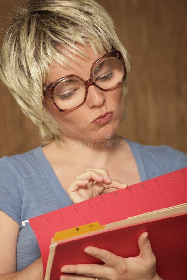 Frau, die durch Dateien schaut stockbild