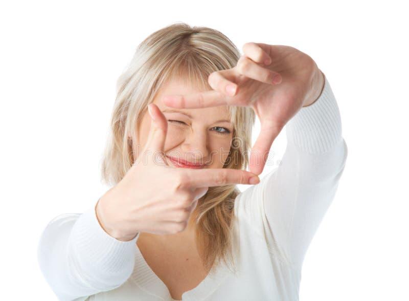Frau, die durch ein Feld gebildet durch ihre Finger schaut lizenzfreie stockbilder