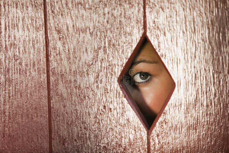 Frau, die durch ein Loch in der Wand schaut stockbilder