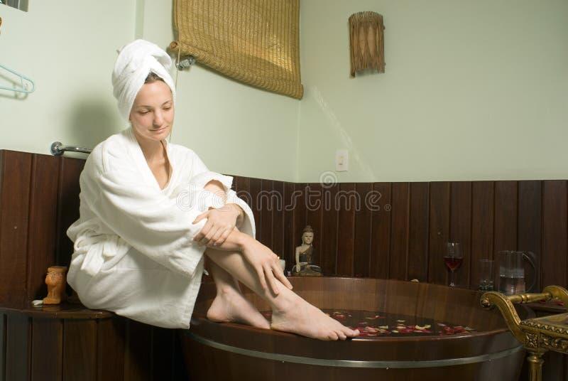 Frau, die durch eine Badekurort-Wanne - horizontal sich entspannt stockbilder