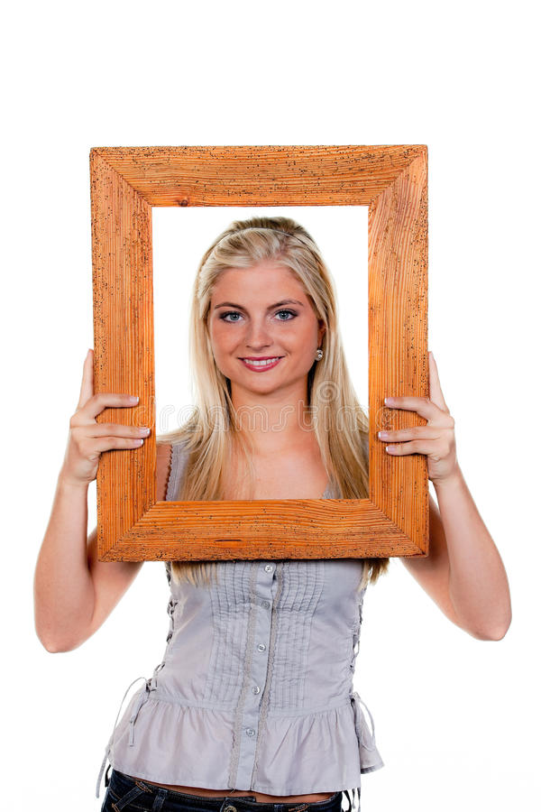 Frau, die durch einen Bilderrahmen schaut stockfotografie