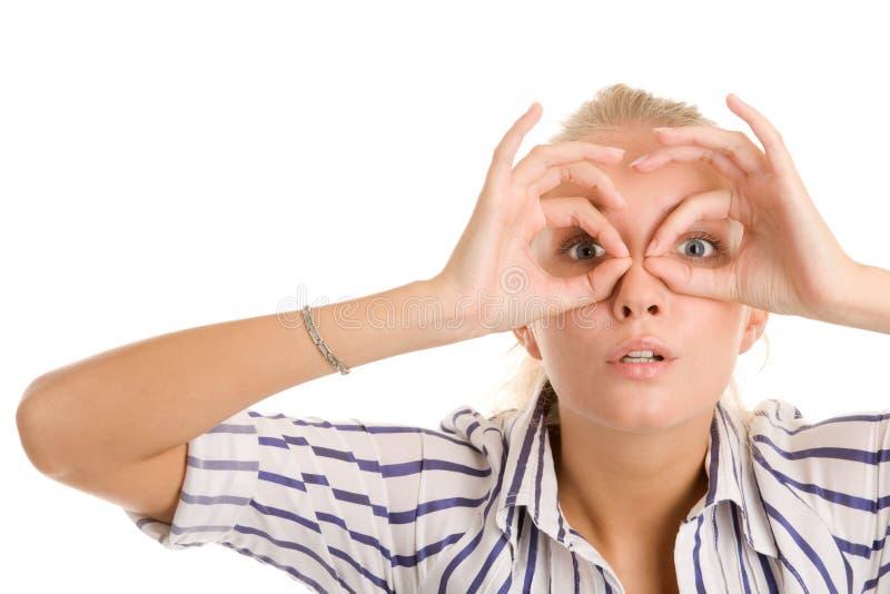 Frau, die durch eingekreiste Finger schaut lizenzfreie stockfotos