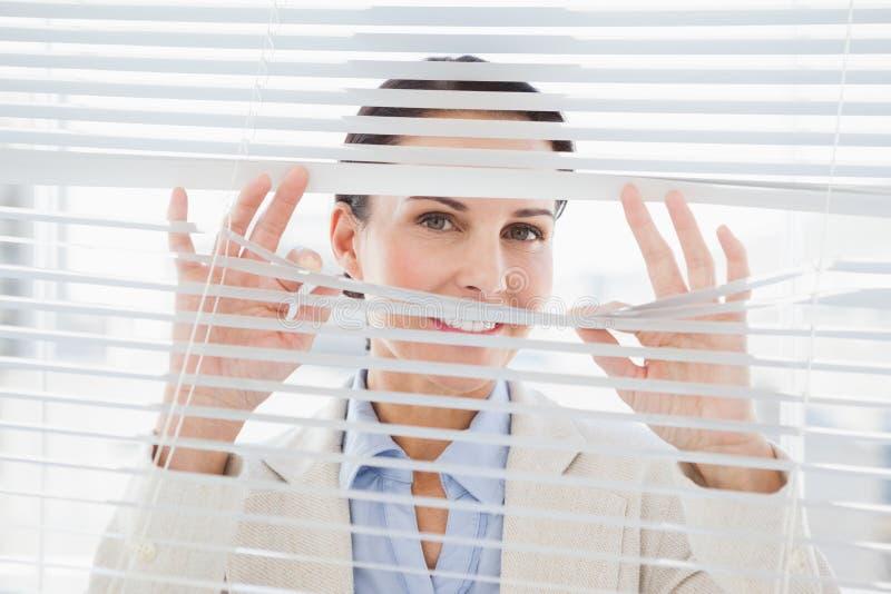 Frau, die durch einige Vorhänge flüchtig blickt stockbild