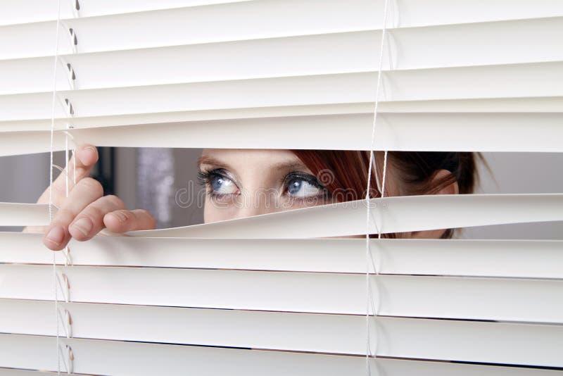 Frau, die durch Fenstervorhänge schaut stockfotografie