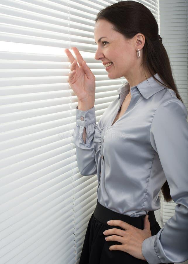 Frau, die durch Fenstervorhänge schaut lizenzfreie stockbilder