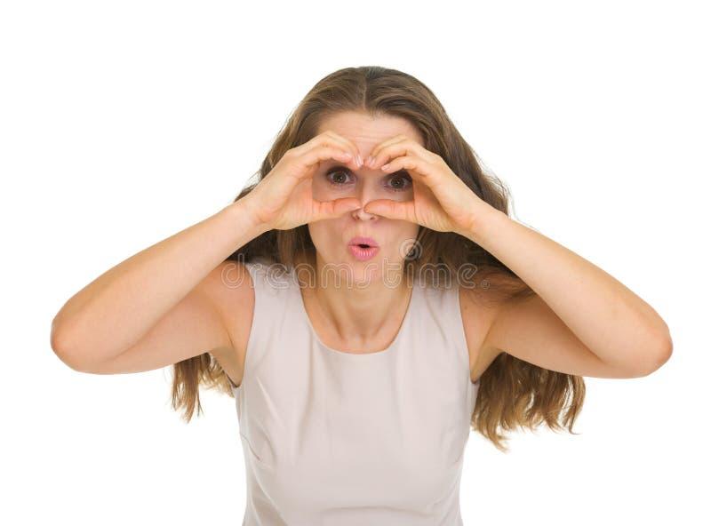 Frau, die durch geformte Hände der Ferngläser schaut lizenzfreies stockfoto