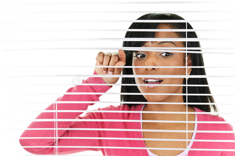 Frau, die durch Jalousien schaut lizenzfreie stockfotografie