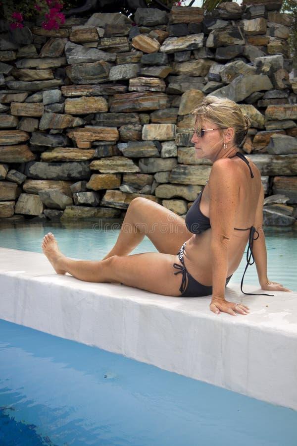 Frau, die durch Pool sitzt lizenzfreie stockfotos