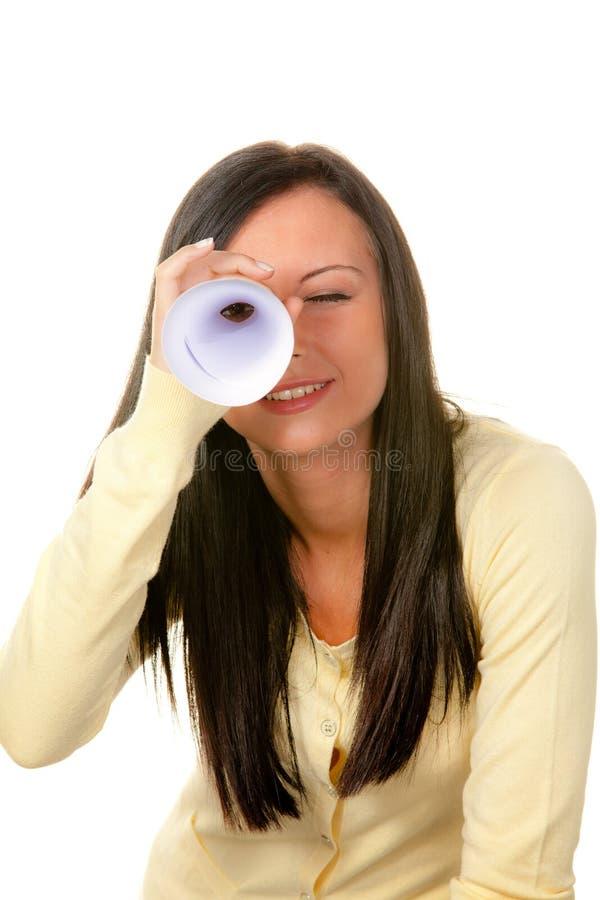 Frau, die durch Rolled-Up Papier schaut stockfoto