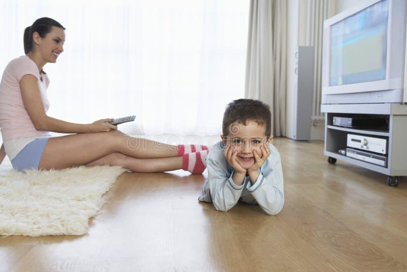Frau, die durch Sohn auf Boden fernsieht lizenzfreie stockfotos