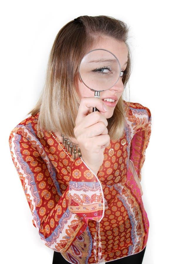 Frau, die durch Vergrößerungsglas über Weiß schaut stockfotos