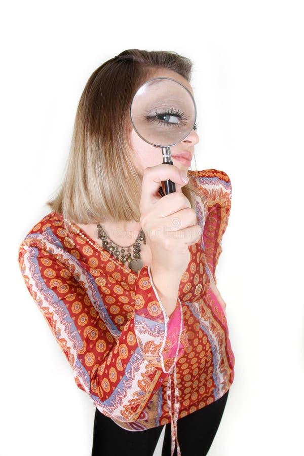 Frau, die durch Vergrößerungsglas über Weiß schaut lizenzfreie stockfotos