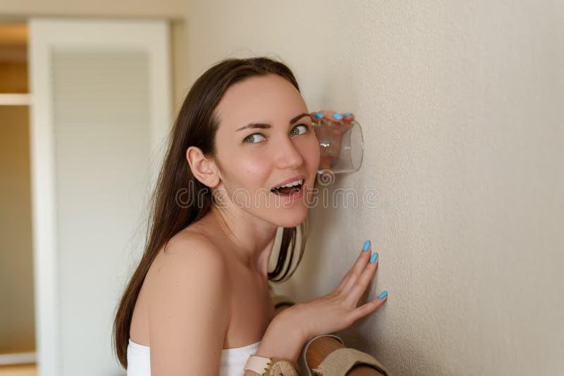 Frau, die durch die Wand des Raumes durch eine Glasschale, Neugier, Spionage, überraschtes Gesicht, klare Gefühle heimlich zuhört stockfoto