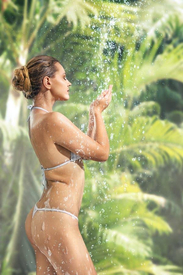 Frau, die Dusche im tropischen BADEKURORT genießt stockfoto